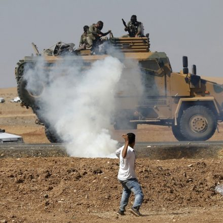 A protester throws stones at an armoured army vehicle during a pro-Kurdish demonstration in solidarity with people of Kobani, near the Mursitpinar border crossing on the Turkish-Syrian border, in the Turkish town of Suruc in southeastern Sanliurfa province October 7, 2014. Islamic State fighters advanced into the south west of the Syrian Kurdish town of Kobani overnight, a monitoring group said on Tuesday, taking several buildings to gain attacking positions from two sides of the city.  REUTERS/Umit Bektas (TURKEY - Tags: CIVIL UNREST MILITARY CONFLICT POLITICS TPX IMAGES OF THE DAY) - RTR498D8