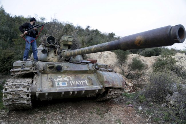 A rebel fighter stands on tank ahead of what rebels said was an offensive to take control of Jisr al-Shughour and surrounding areas, controlled by forces loyal to President Assad